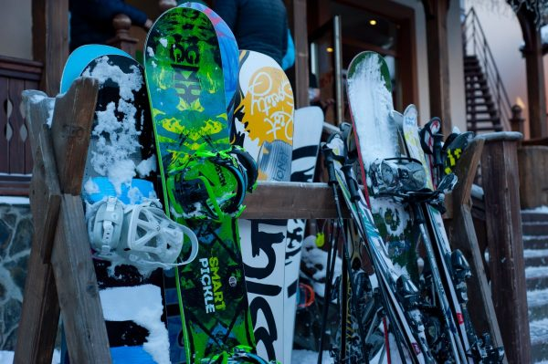 Snowboard equipment leaning against the racks at a ski resort || 1849 Mountain Rentals
